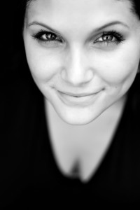 Close up of a beautiful young womans face with a friendly smile. Shallow depth of field.
